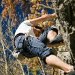 Foto de Stock  : Man climbing a rock short