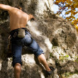 Foto Stock: Man climbing a rock short