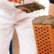 Bricklayer with brick at a — Stock Photo #5023568