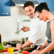 Stock Photo: Young couple cooking - man