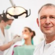 Dentist in his surgery looking at — Stock Photo
