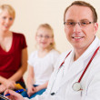 Pediatrician with family - mother - Stock Photo
