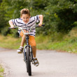 Little Boy riding his bicycle on a — Stock Photo