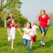 Happy family playing football - Stockfoto