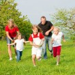 Happy family playing football — Stock Photo