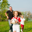 Happy family playing football — Stock Photo #5024351