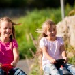 Two sisters with toy cars - Stock Photo