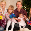 Family in front of a Christmas tree — Stock Photo #5024657
