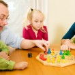 Family playing a board game at - Stock Photo