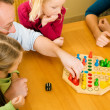 Family playing a board game at — Stock Photo #5024752