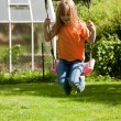 Little girl child sitting on a swing — Stock Photo