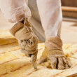 Man cutting insulation material for building - Stock Photo