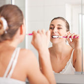 Young woman brushing teeth at wash bowl — Stock Photo