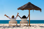 Couple sitting in sun chairs — Stock Photo