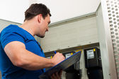 Technician reading the electricity meter — Stock Photo