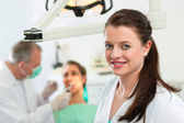 Dentist in his surgery looking at — Foto Stock