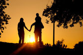 Family having a walk at sunset — Stock Photo