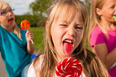 Three girls eating lollipops, the — Stock Photo