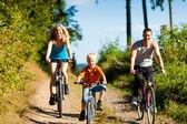 Rodina s dítětem na kolech — Stock fotografie