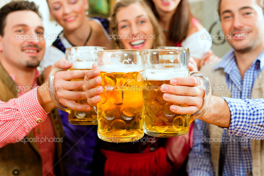 Group of five young men and women in traditional Tracht drinking beer and having a party with beer   Stock Photo #5022727