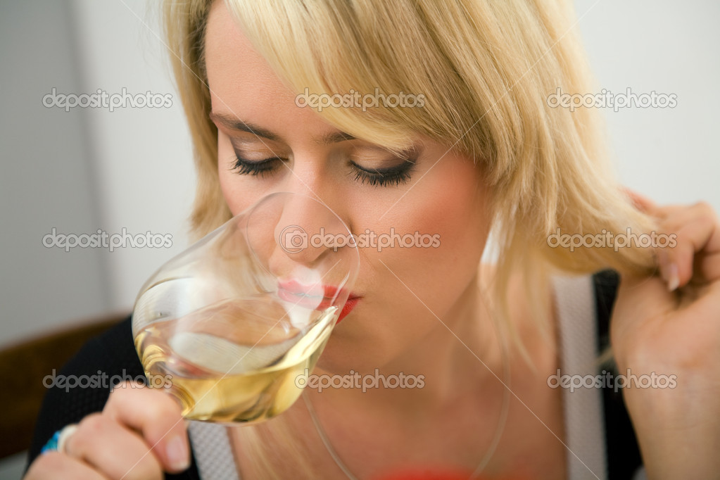 Woman enjoying a zip of white wine — Stock Photo #5023643