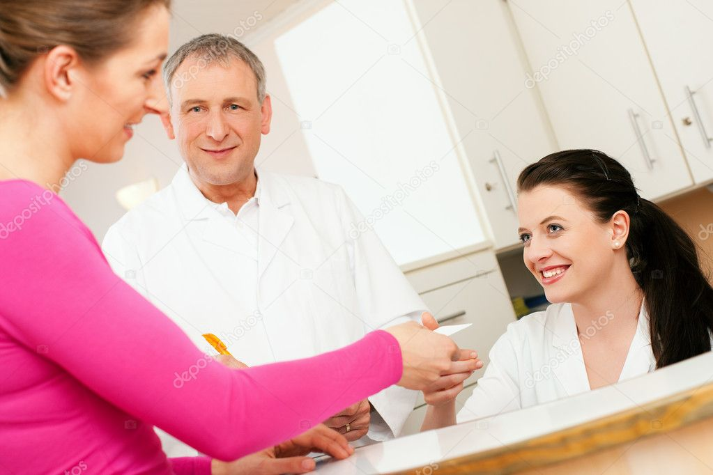 Office of doctor or dentist, handing her health insurance card over the counter to the nurse, the doctor standing in the background  — Stock Photo #5023737