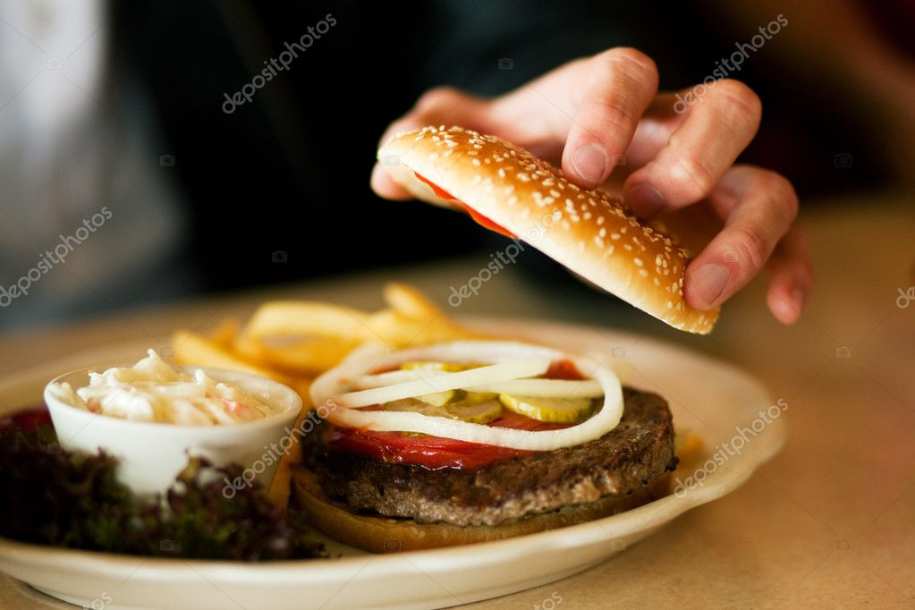 Eating a hamburger opening it to look inside, shot with available light — Stock Photo #5023766