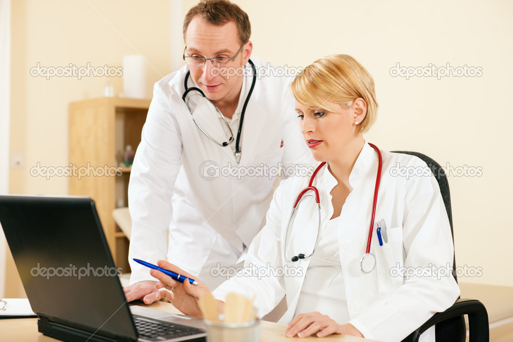 Discussing test reports that show on their laptop screen  — Stock Photo #5023928