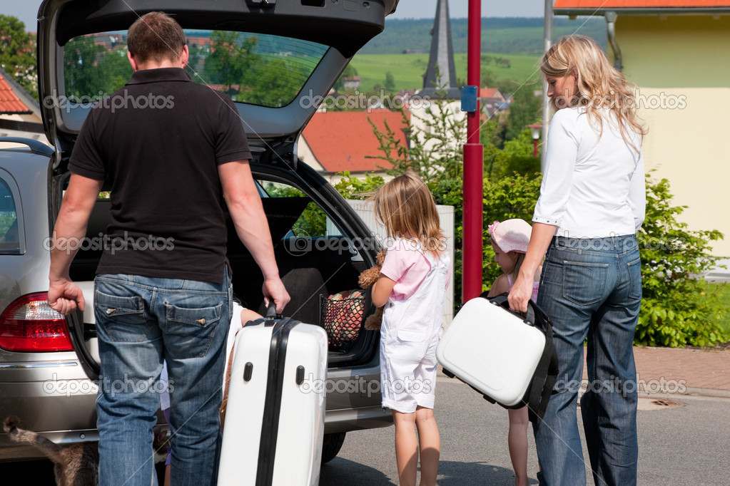 Family with three kids attempting to head off for the trip to their vacation loading kids and luggage in the car — Stock Photo #5024314