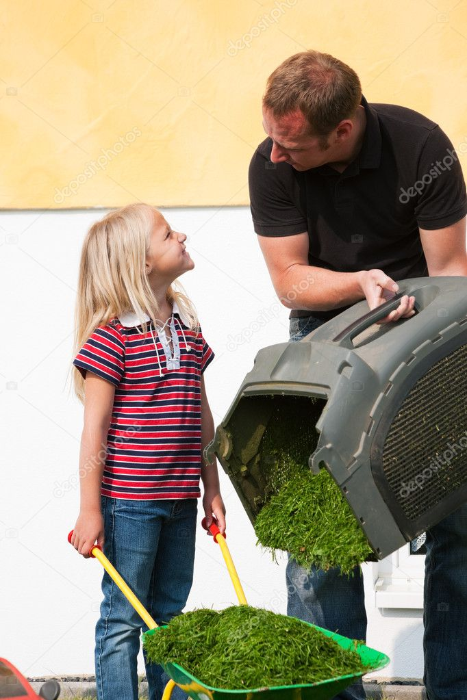 Lawn together, daddy has a real lawnmower, the daughter a toy version and is a bit jealous  — Stock Photo #5024425