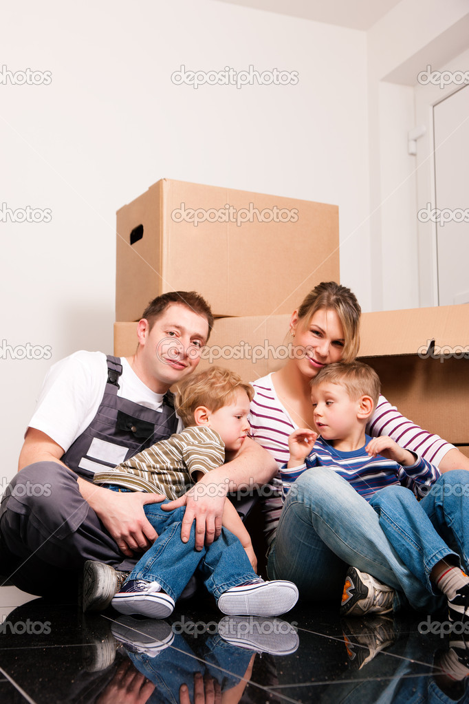House. They are sitting in front of a stack of moving boxes being happy. Father is dressed in a way that can also represent a mover  — Stock Photo #5024499