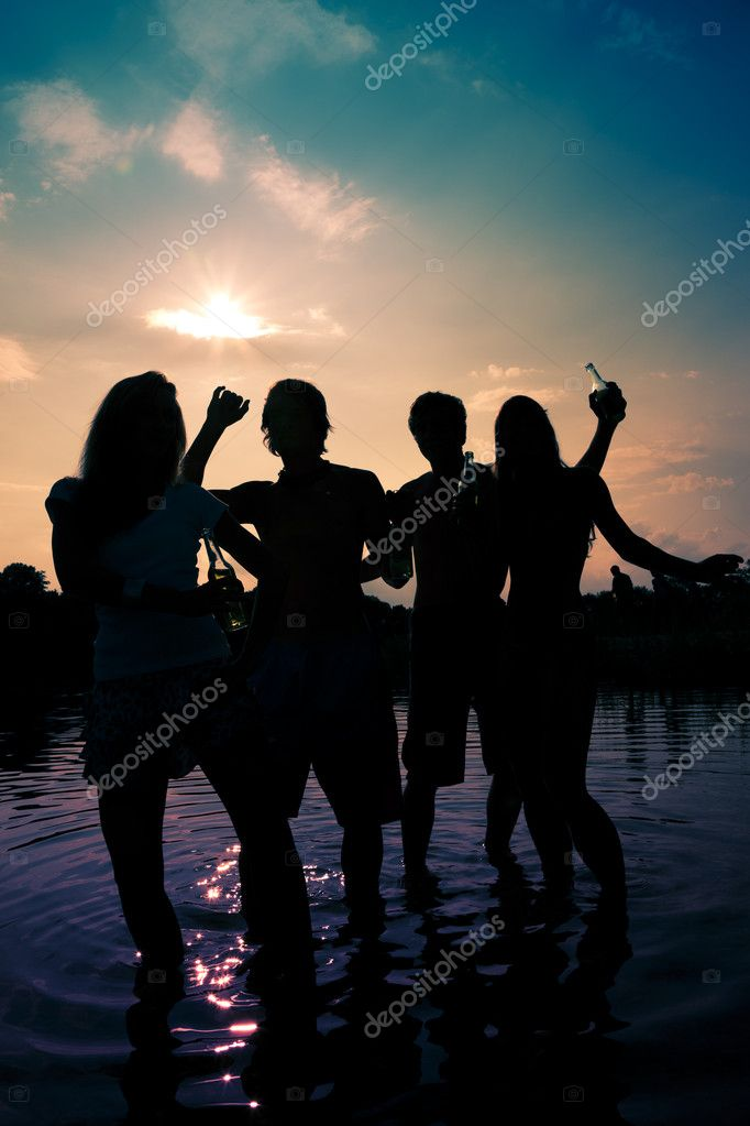 Beach dancing to music, drinking and having a lot of fun in the sunset - only silhouette of to be seen — Stock Photo #5025121