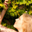 Young woman looking on a grape - Stock Photo