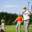Senior couple playing golf on a — Stock Photo #5050578