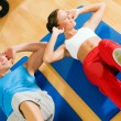Sportive couple doing sit-ups - Stock Photo