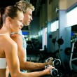 Couple in the gym, rivaling each — Stock Photo