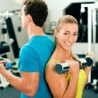 Stock Photo: Couple in the gym, rivaling each