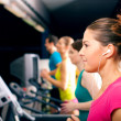 Running on treadmill in gym - Stock Photo