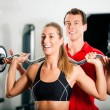 Woman in gym with personal — Stock Photo