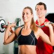 Woman in gym with personal — Stok fotoğraf