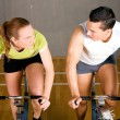 Couple using bikes in a fitness — Stock Photo