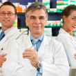 Pharmacist with customers in - Stock Photo