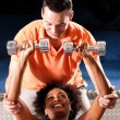 Stock Photo: Young woman lifting a dumbbell