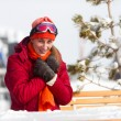 Woman sitting in front of a ski — Stock Photo