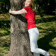 Girl cuddling a tree and — Stock Photo
