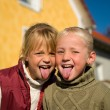 Sisters sticking their tongue - Stockfoto
