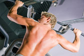 Hombre fuerte haciendo dominadas en un — Foto de Stock