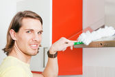 Man dusting his apartment — Stock Photo