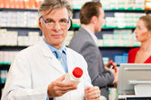 Pharmacist with customers in — Stock Photo