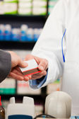 Pharmacist with customer in — Stock Photo